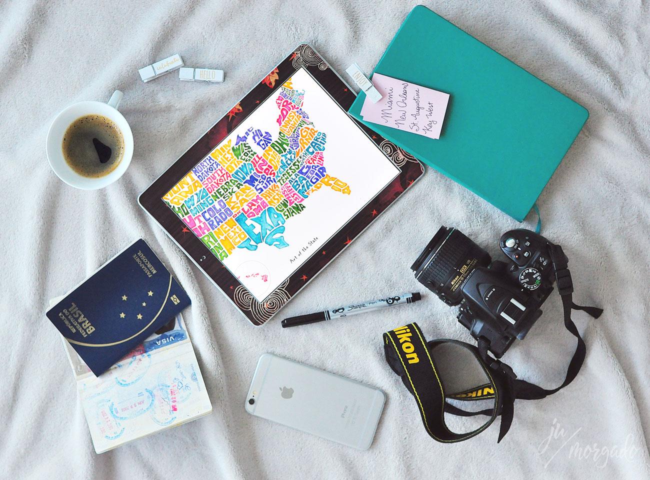 Foto com vários itens para planejar uma viagem. Um caderno, uma câmera, um mapa, o passaporte.
