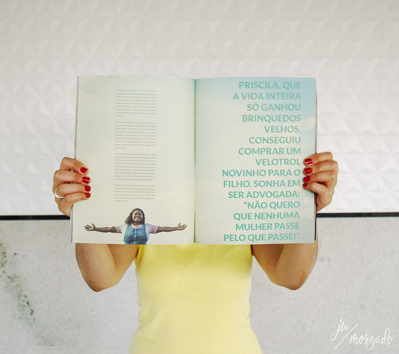 Alguém segura uma revista na frente do rosto, página aberta na matéria da Priscila.