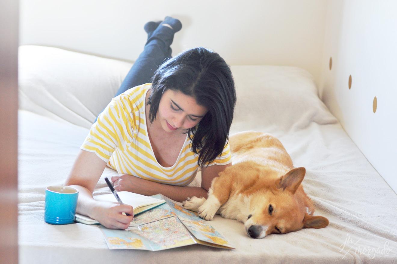 Ju deitada na cama planejando a viagem com o cachorro Freddie ao lado.