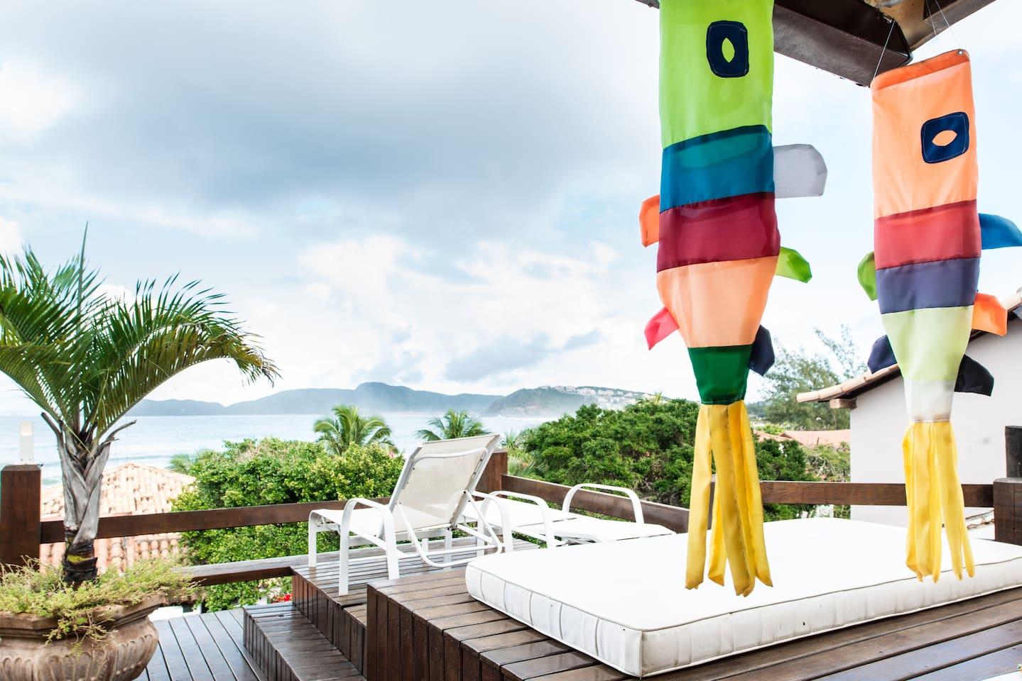 Casa de Búzios que vamos alugar, na foto tem cadeiras em frente a uma vista de praia